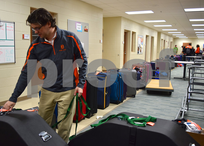 Drumline Instructor Austin Shoupe ties cords around tenor drums in preparation for the DeKalb High  School Marching Barbs' flight to Ireland on Sunday. The luggage and instruments of the band's 102 members and 11 chaperones are organized into a line behind Shoupe. The group left Sunday for an eight-day trip to Ireland, where they will perform in the St. Patrick's Festival Parade in Dublin.