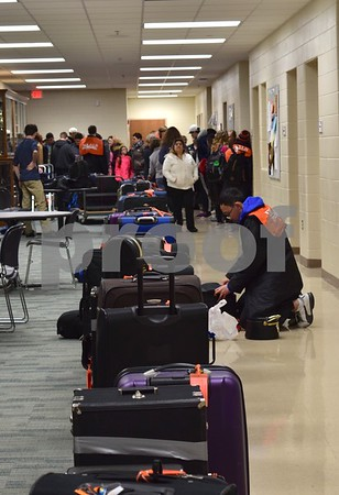 The luggage and instruments of the 102 members of the DeKalb High School Marching Barbs and 11 chaperones are organized into a line before being loaded onto school buses Sunday.