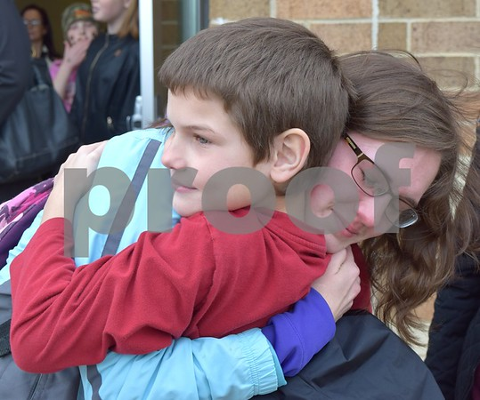 DeKalb High School Senior Amber Boyd tearfully hugs her 10-year-old brother Jared goodbye before boarding a school bus to O'Hare International Airport in Chicago on Sunday. Boyd is one of 102 members of the DHS Marching Barbs traveling to Ireland for an eight-day trip.