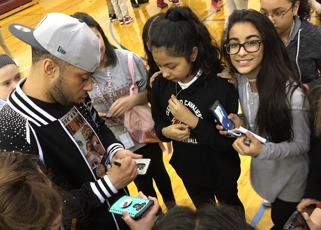 . Richard Payerchin - The Morning Journal <br> A member of the Cleveland Cavaliers Scream Team signs a cell phone of a scholar at Lorain City Schools\' General Johnnie Wilson Middle School on March 22, 2018. Cavs\' representatives visited the school to present a $1,000 check for the Cavs\' Straight �A� All-Stars program, presented by Westfield Insurance.