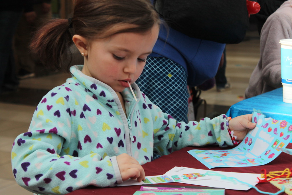 . Kristi Garabrandt � The News-Herald <br> Gigi Kumel, 4, of Mentor selects stickers for the bookmarker she made during the Kidshow at Great Lakes Mall on March 24.