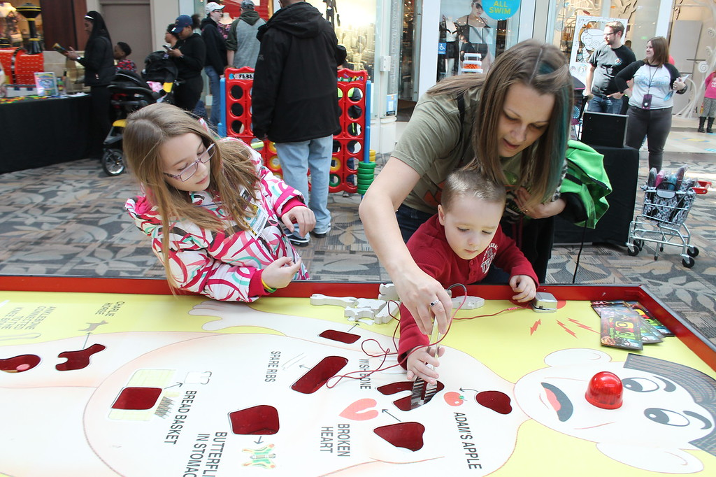 . Kristi Garabrandt � The News-Herald <br> Danielle Mayse, 8, along with Angelique and Matthew Seese, 4, all of Mentor,  try their hands at the Game of Operation during the Kidshow at Great Lakes Mall on March 24.