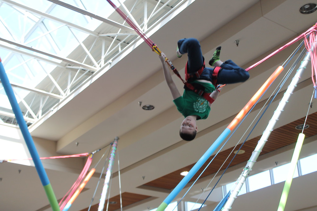 . Kristi Garabrandt � The News-Herald <br> Payton Barnett,10, of Willowick does a flip while trying out the bungee jumping exhibit during the Kidshow at Great Lakes Mall on March 24.