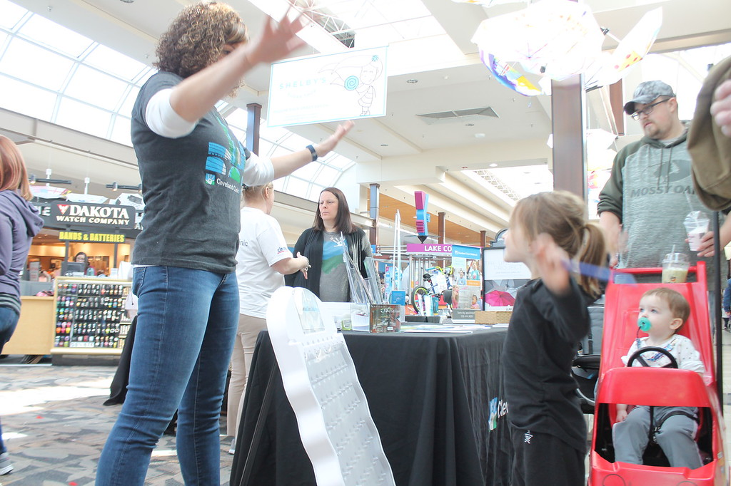 . Kristi Garabrandt � The News-Herald <br> Kennedy Stallard, 4, of Eastlake does arm circles with an exhibitor from Cleveland Clinic to claim the prize she won after playing Plenco during the Kidshow at Great Lakes Mall on March 24.