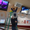 On March 14, Brandon Partridge, general manager of Pinheadz at Idle Hour Lanes, installs black lights for cosmic bowling while standing on a ladder. He is assisted by Ryan Auberry. Cosmic bowling is one of many additions to the bowling alley after it changed hands last month.