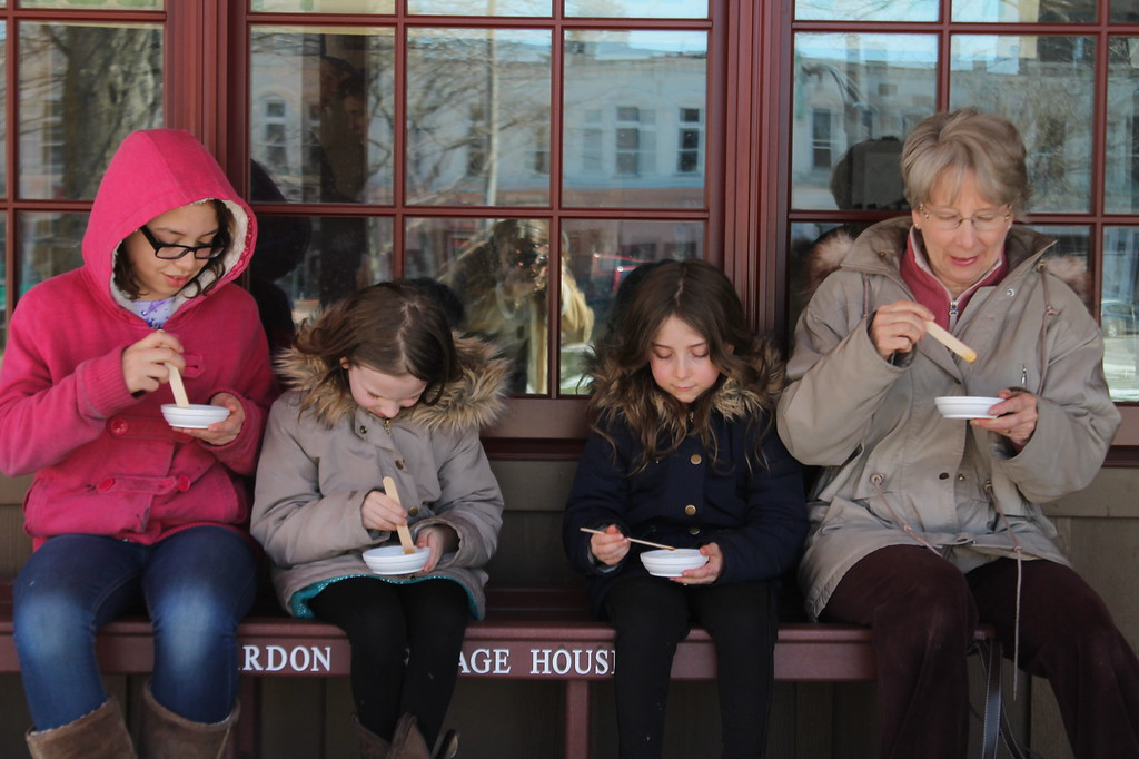 . Kristi Garabrandt - The News-Herald <br> Mary Dove of Hambden and her three granddaughters: Emily Dove, 10, Faith Francis, 8, and Hope Francis 6, sit on a bench outside the new Heritage House Sugarhouse on the Square in Chardon eating maple stirs.  For the Dove family this is a tradition that has spanned three generations.