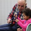 Arriana,4, sits with her dad and uses rythym sticks to keep tempo during the reading of One Stuck Duck while at Special Needs Story Time.<br /> Kristi Garabrandt  The News-Herald