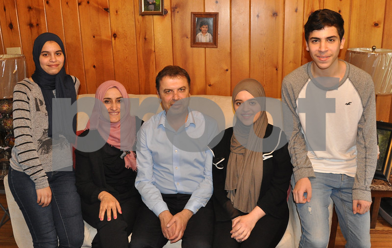 Five members of the Alkarzon family gathered for a photo in their home on Normal Road in DeKalb. From left are Nour, Manal, Awni, Hend and Bashar Alkarzon. Two other children, Mohammed and Maha, were not present.