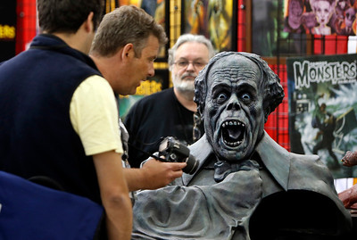 Brent Armstrong, background, watches visitors to the Big Wow Comic Festival admire his Lon Chaney sculpture at the San Jose Convention Center in San Jose, Calif., on Sunday, May 18, 2014. (Karl Mondon/Bay Area News Group)