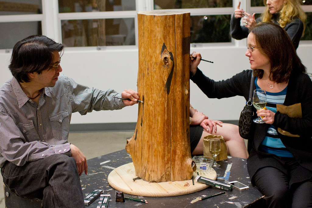 . Artist Chris Sicat and Karen Valladao, a board member, use pencils to cover a wood stump with graphite as part of the hands-on demonstration during the Pencils Down opening celebration at the Palo Alto Art Center on Friday, Jan. 24, 2014. Pencils Down is a winter exhibition that focuses on artist who use graphite as a medium. For more information, visit the Palo Alto Art Center at www.cityofpaloalto.org (Kirstina Sangsahachart/ Daily News)
