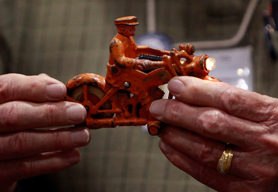 Chuck Stone, of Pear Valley, inspects a 1930's cast iron motorcycle toy at the Toy & Model Train Expo at the Santa Clara Convention Center, Saturday morning, March 1, 2014 in Santa Clara, Calif. The Humbley motorcycle, with a working headlight, was brought by Jim Friedman, left foreground. (Karl Mondon/Bay Area News Group)