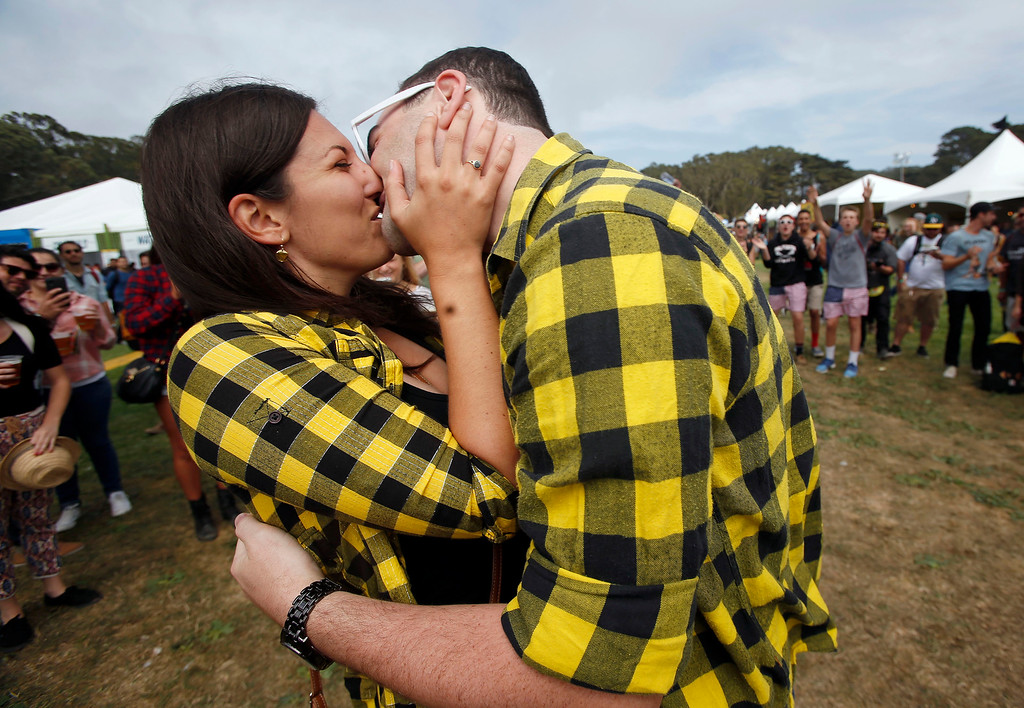 . Michelle Kitson, left, and Brett Bellon, of San Diego, kiss after Bellon proposed to her during day one of the Outside Lands music festival at Golden Gate Park in San Francisco, Calif., on Friday, Aug. 8, 2014. (Jane Tyska/Bay Area News Group)