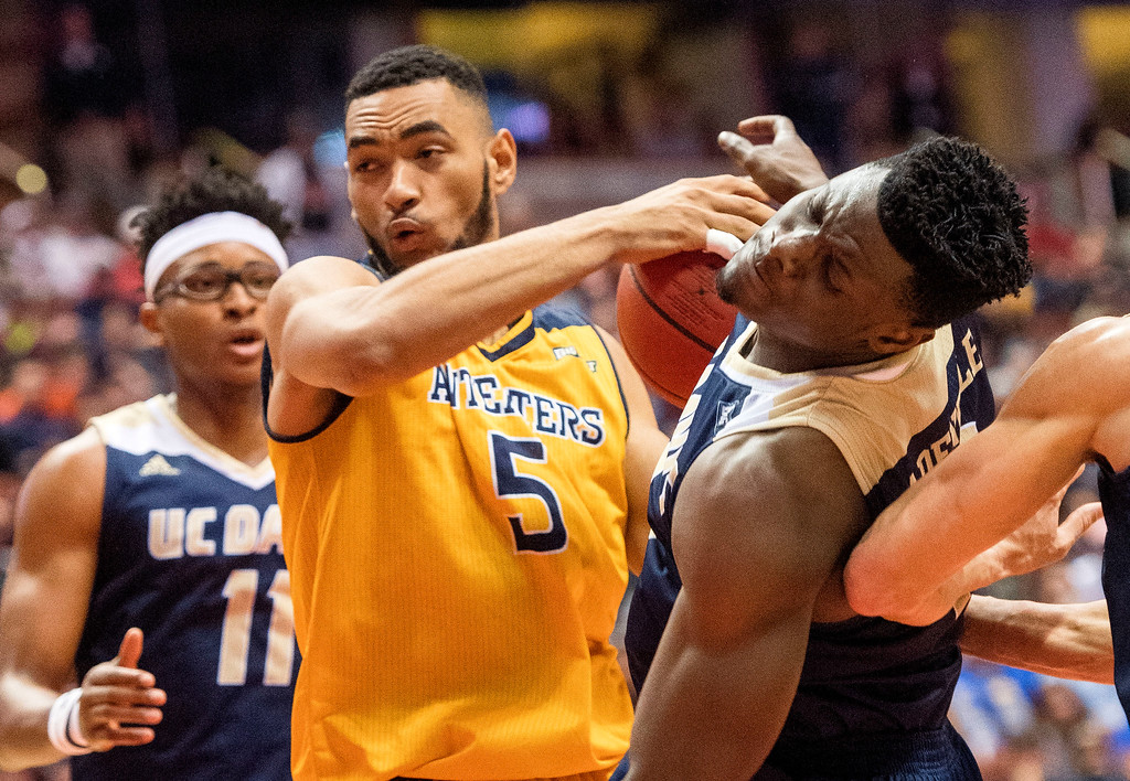 . UC Irvine forward Jonathan Galloway, center, turns to go to the basket and hits UC Davis forward J.T. Adenrele in the chin during the Big West Tournament Championship game in Anaheim on Saturday, March 11, 2017. (Photo by Paul Rodriguez, Orange County Register/SCNG)