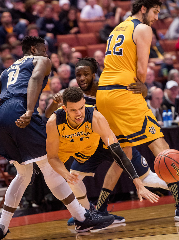 . UC Irvine guard Luke Nelson, center, is tripped up by UC Davis forward J.T. Adenrele in the first half of the Big West Tournament Championship game in Anaheim on Saturday, March 11, 2017. (Photo by Paul Rodriguez, Orange County Register/SCNG)