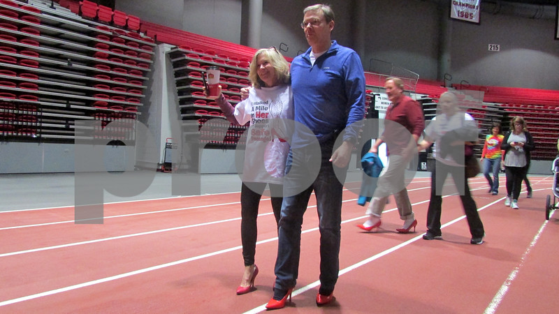 Tarryn Thaden helps Art Bingham walk in red high heels Saturday morning as part of Walk a Mile in Her Shoes at the Northern Illinois University Convocation Center.
