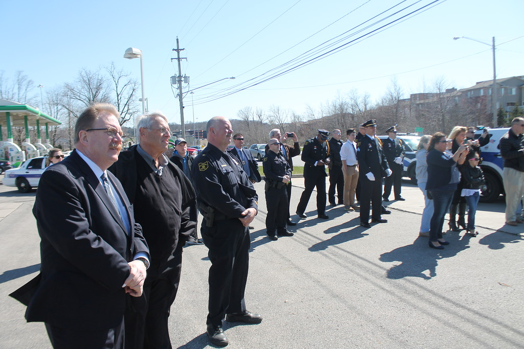 . Kristi Garabrandt � The News-Herald <br> State Rep. John Rogers, former Willoughby Mayor David Anderson and Willoughby Police Chief Jack Beckwith along with Willoughby police officers and friends and family of fallen officer Jason Gresko  watch the unveiling of a highway memorial sign dedicated in his honor on state Route 91 in Willoughby on April 20, 2018.