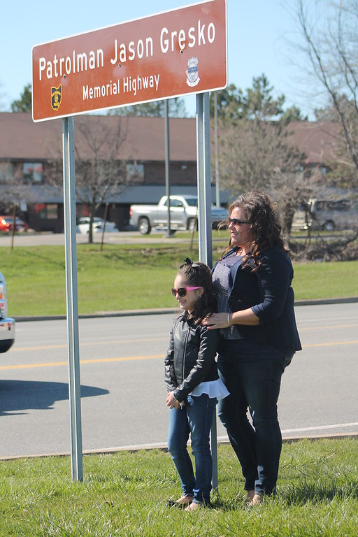. Kristi Garabrandt � The News-Herald <br> Sandra and Olivia Gresko, wife and daughter of fallen officer Jason Gresko  stand by the memorial sign erected in his honor on Route 91 in Willoughby on April 20, 2018.