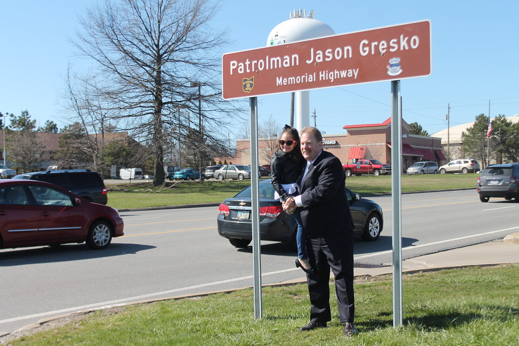 . Kristi Garabrandt � The News-Herald <br> State Rep. John Rogers holds Olivia Gresko under the sign erected on Route 91 to honor her father Jason Gresko who was killed in the line of duty.