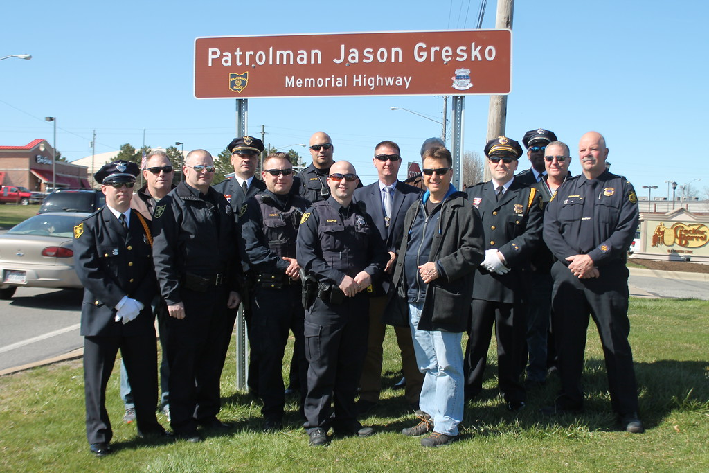 . Kristi Garabrandt � The News-Herald <br> Police Chief Jack Beckwith and members of the Willoughby Police Department  stand by the memorial sign erected in honor of fallen Willoughby officer Jason Gresko on Route 91 in Willoughby on April 20.
