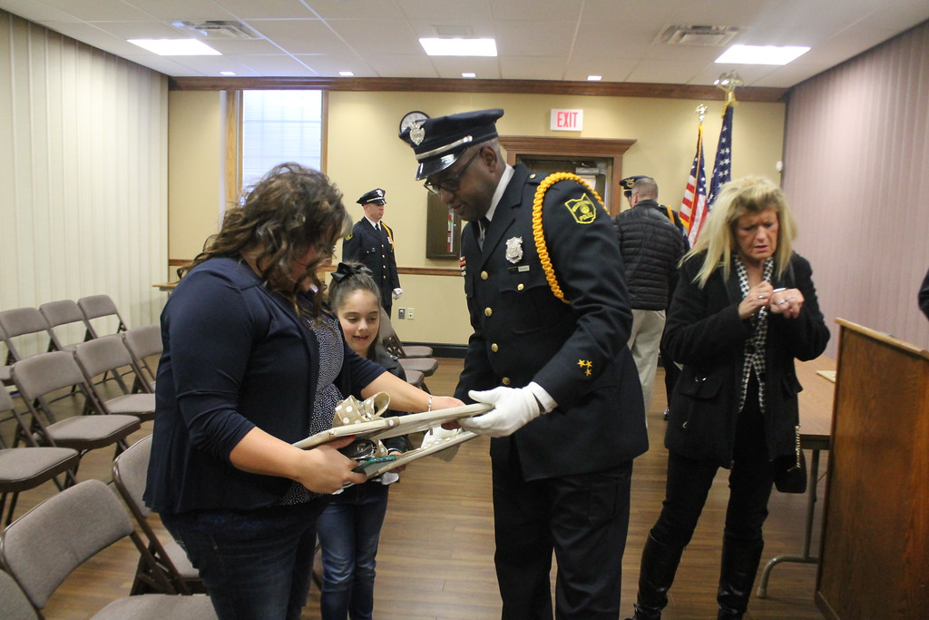 . Kristi Garabrandt � The News-Herald <br> A Willoughby police officer and Honor Guard member presents Sandra and Olivia Gresko, wife and daughter of fallen officer Jason Gresko with miniature replicas of the  memorial signs erected on State Route 91 in Willoughby in Jason\'s honor on April 20, 2018.