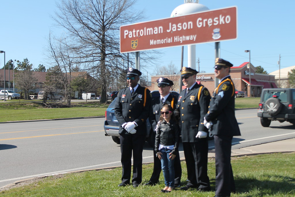 . Kristi Garabrandt � The News-Herald <br> The Willoughby Police Department Honor Guard stand  with Olivia Gresko, daughter of  fallen officer Jason Gresko   by the memorial sign erected in his honor on Route 91 in Willoughby on April 20.