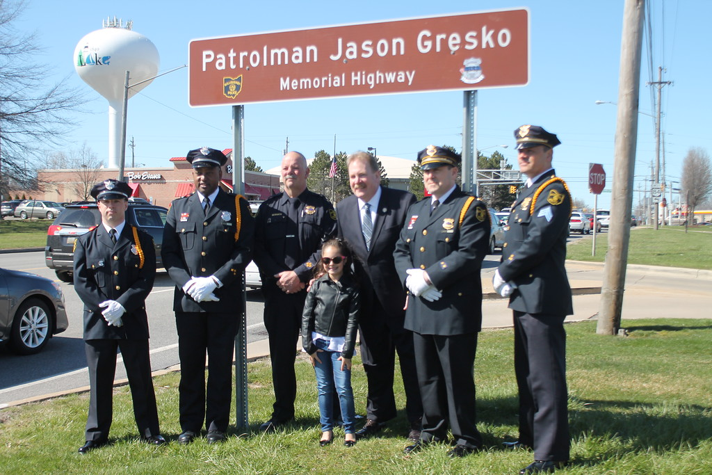 . Kristi Garabrandt � The News-Herald <br> Willoughby Police Chief Jack Beckwith,  State Rep. John Rogers and The Willoughby Police Department Honor Guard stand  with Olivia Gresko, daughter of  fallen officer Jason Gresko by the memorial sign erected in his honor on Route 91 in Willoughby on April 20.
