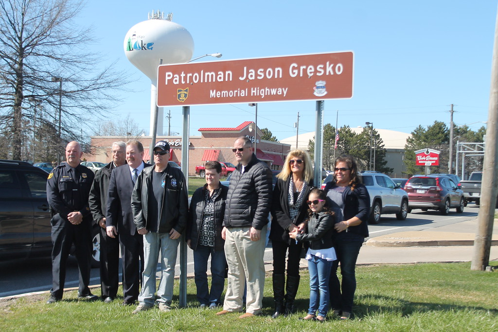 . Kristi Garabrandt � The News-Herald <br> Willoughby Police Chief Jack Beckwith, former  Willoughby Mayor David Anderson and State Rep. John Rogers stands  with family of fallen officer Jason Gresko by the memorial sign erected in his honor on Route 91 in Willoughby on April 20, 2018.