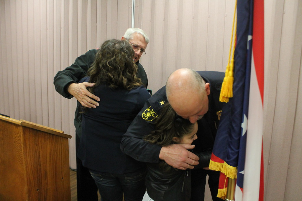 . Kristi Garabrandt � The News-Herald <br> Former Willoughby Mayor David Anderson hugs  Sandra Gresko, the widow of fallen Willoughby officer Jason Gresko while Willoughby Police Chief  hugs Gresko\'s daughter Olivia at the end of the  dedication ceremony for route 91 in  Gresko\'s memory at Willoughby City Hall on April 20