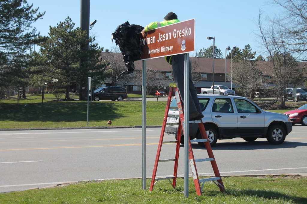 . Kristi Garabrandt � The News-Herald <br> Mike Gillispie, of the Willoughby Traffic Division unveils one of the two signs placed on Route 91 in Willoughby to honor fallen officer Jason Gresko, April 20, 2018.