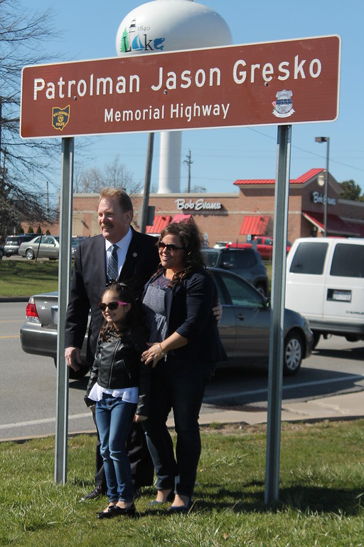 . Kristi Garabrandt � The News-Herald <br> State Rep. John Rogers stands with Sandra and Olivia Gresko, wife and daughter of fallen officer Jason Gresko  by the memorial sign erected in his honor on Route 91 in Willoughby on April 20, 2018.
