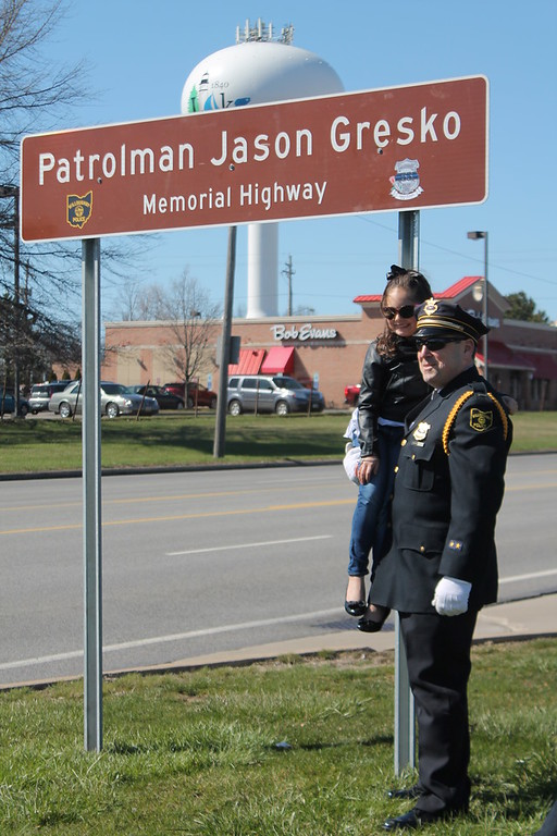 . Kristi Garabrandt � The News-Herald <br> Willoughby Police Lieutenant Matt Tartaglia holds Olivia Gresko under the sign erected on Route 91 to honor her father Jason Gresko who was killed in the line of duty.