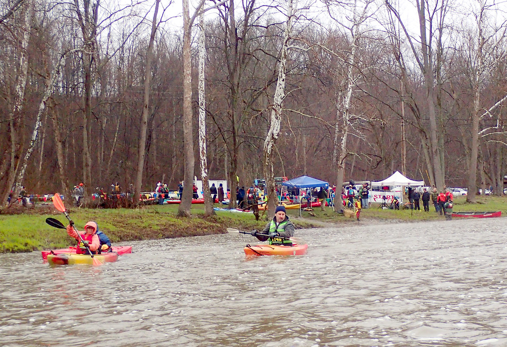 . Jonathan Tressler � The News-Herald <br> Three by three, paddlers in the 2018 Grand River Canoe and Kayak race propel themselves downstream from the starting point near the covered bridge in Harpersfield Township April 28.