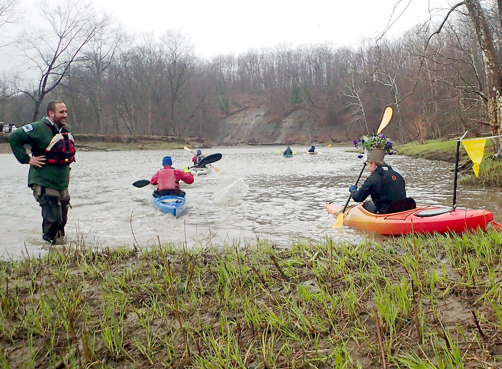 . Jonathan Tressler � The News-Herald <br> Chardon Township resident Megan Pinzone, at far right, pushes off from the starting line at the 2018 Grand RIver Canoe and Kayak Race just downstream from the Harpersfield Covered Bridge, in Ashtabula County�s Harpersfield Township, while sporting her honorable mention-garnering flower-pot hat as a Lake Metroparks official looks on with a grin.