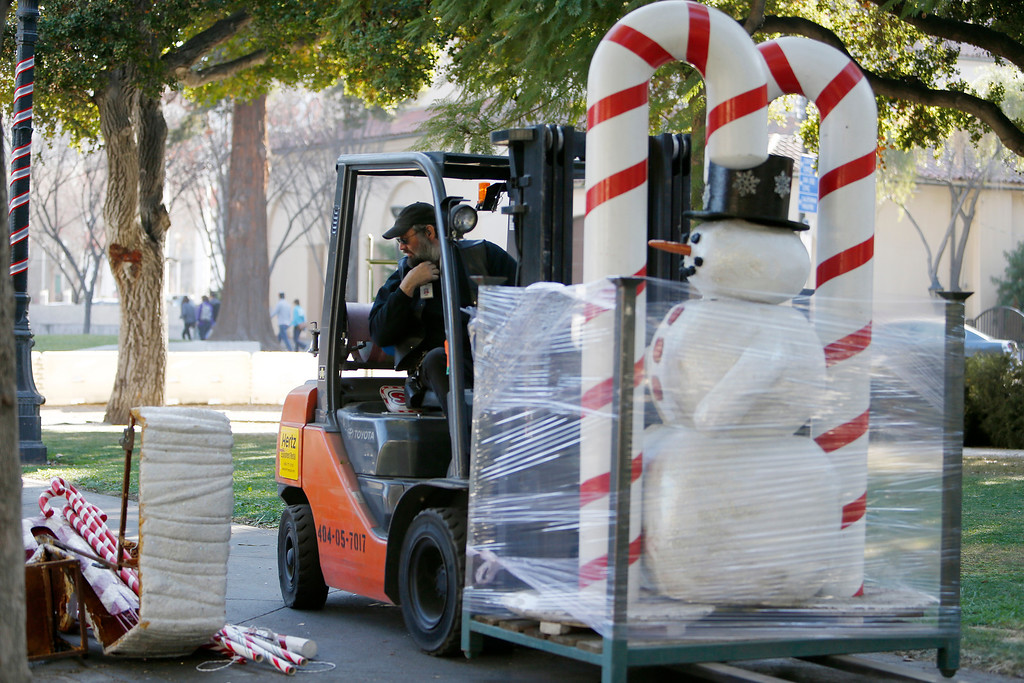 . James Hilmer drives away with Frosty the Snowman during cleanup at Christmas in the Park in downtown San Jose, Calif., on Saturday, Jan. 4, 2014. (Josie Lepe/Bay Area News Group)