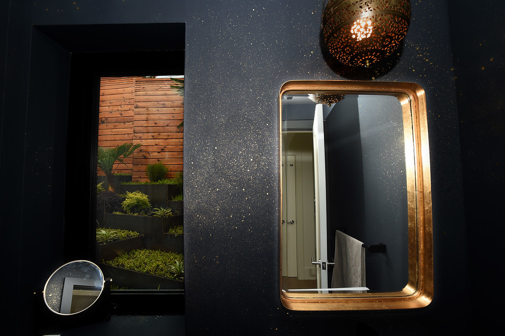 . A vintage pierced Moroccan pendant in brass with door metal colored walls and flecks of gold are featured in this bathroom with a terraced garden view out the window of this Sunset\'s 2016 Idea House in Berkeley, Calif., on Monday, Aug 22, 2016.  (Susan Tripp Pollard/Bay Area News Group)