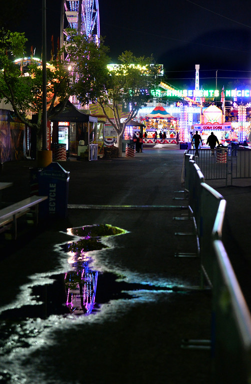 . The reflection of a Ferris wheel is cast in a puddle at the Alameda County Fair on Thursday, June 26, 2014. (Doug Duran/Bay Area News Group)