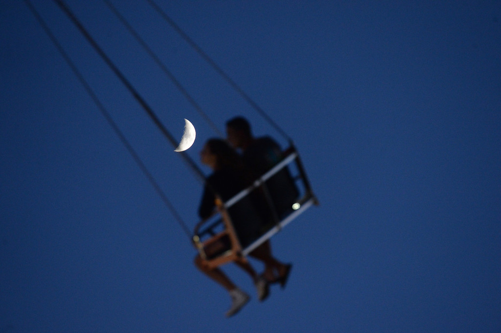 . With the moon overhead, fairgoers ride the Vertigo carnival ride at the Alameda County Fair in Pleasanton, Calif., on July 3, 2014. (Doug Duran/Bay Area News Group)