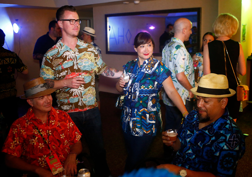 """. Chad \""""Woody\"""" Greenwood, wife Tonya Greenwood and Ignacio \""""Noch\"""" Gonzalez, of the Bay Area, converse at an evening party in a suite hosted by  Mark Holt at the 16th Annual Tiki Oasis \""""Party on Monster Island,\"""" at the Crown Plaza, formerly the Hanalei Hotel in San Diego, Calif., on Friday, August 19, 2016. (Josie Lepe/Bay Area News Group)"""