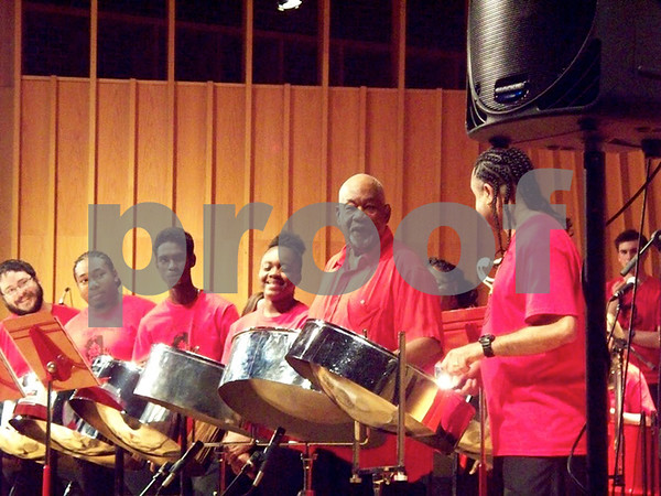 "NIU Steelband students watch director Cliff Alexis (second from right) and Liam Teague (right) share a musical conversation as they perform ""Take a Break Today"" on Sunday night during a tribute concert honoring Alexis' years at NIU."