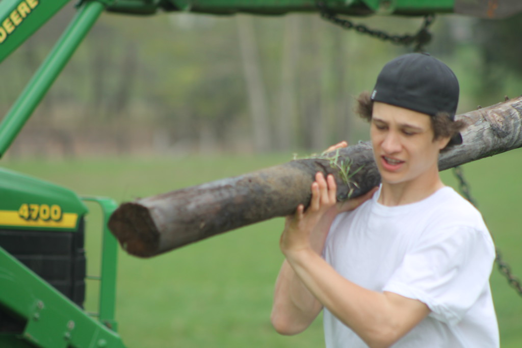 . Shane Callahan, freshman, Chardon High School,  carries  a wood post from and old being torn dorn  to clear the way for a new vinyl one during their community service field trip at Santa\'s Hide-A-Way Hollow in Middlefield on May 3. Kristi Garabrandt - The News-Herald