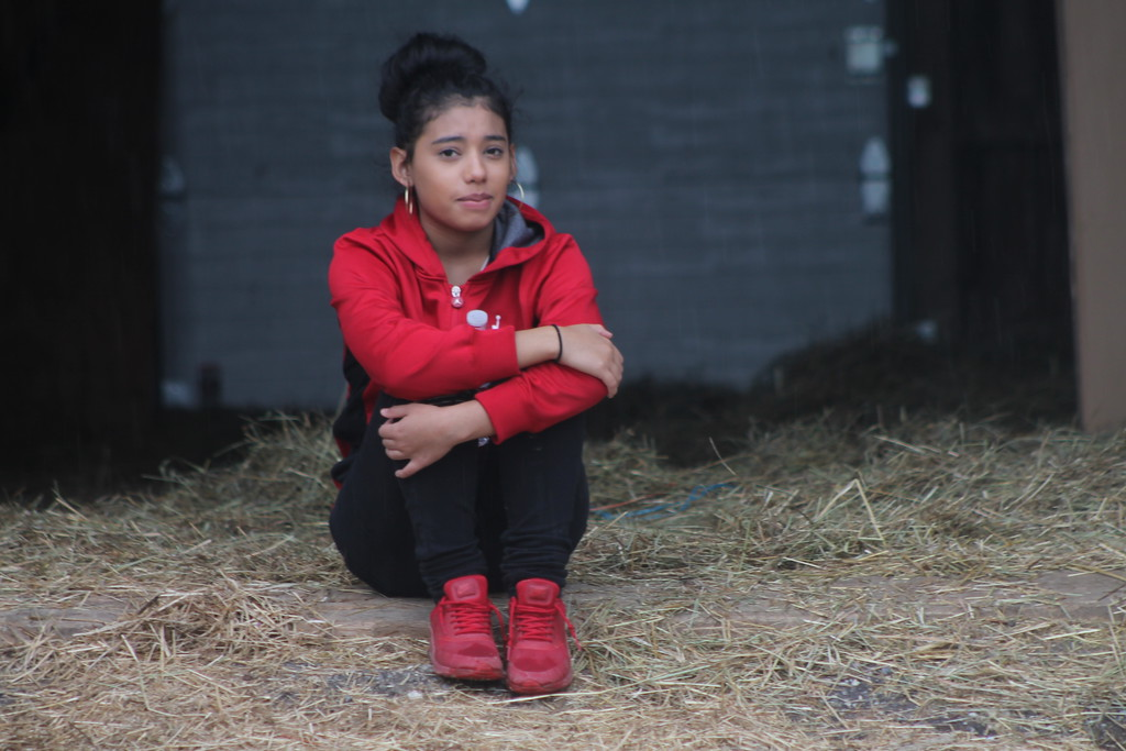 . Selena Hernandez, freshman at   Chardon High School takes a break  during the school\'s community service field trip at Santa\'s Hide-A-Way Hollow in Middlefield on May 3. Kristi Garabrandt - The News-Herald