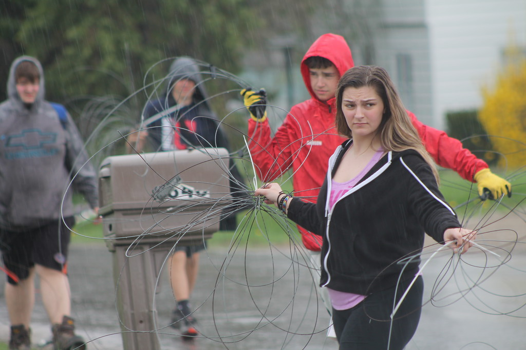 . Students from Chardon High School work in the rain to  remove a wood post and wire fence to clear the way for a new vinyl one during their community service field trip at Santa\'s Hide-A-Way Hollow in Middlefield on May 3. Kristi Garabrandt - The News-Herald
