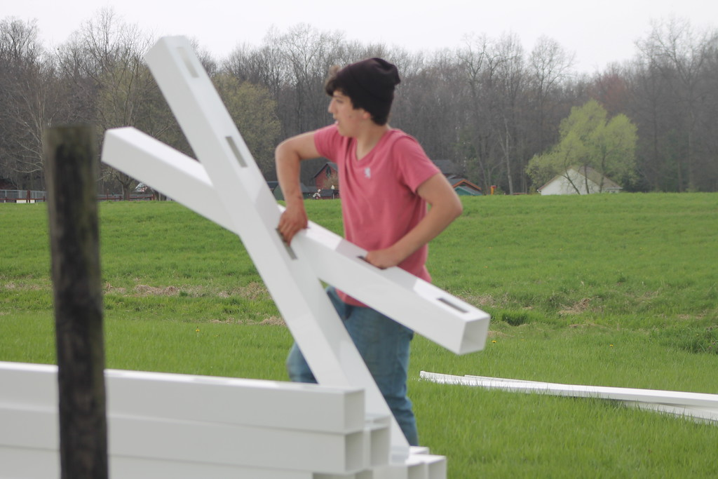 . Dylan Buckels  a freshman at Chardon High School lays out vinyl fence pieces during the school\'s  community service field trip at Santa\'s Hide-A-Way Hollow in Middlefield on May 3. Kristi Garabrandt - The News-Herald