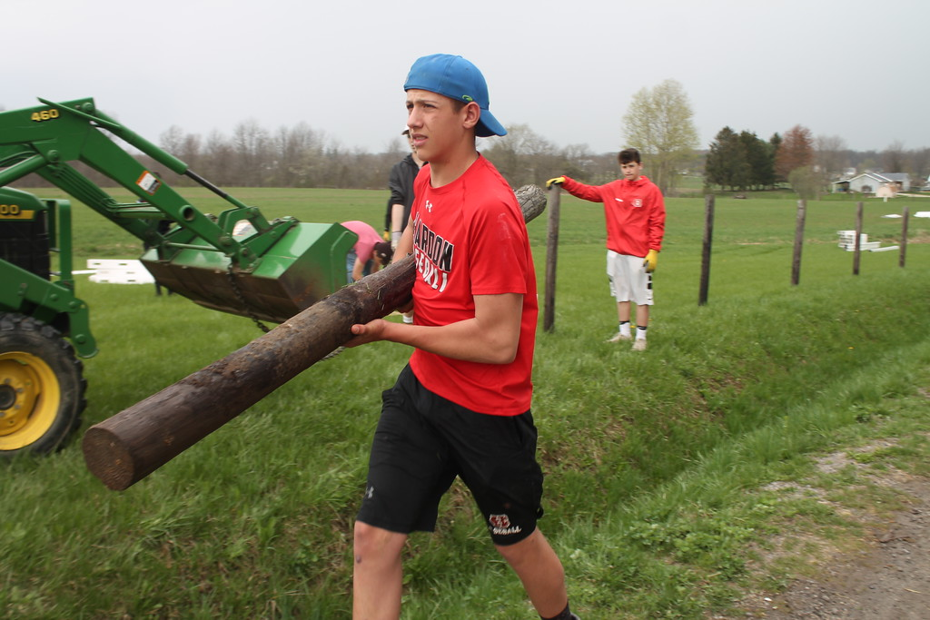 . Brandon Schreffler, freshman,  Chardon High School carries a fence post from a fence the students are removing during their community service field trip at Santa\'s Hide-A-Way Hollow in Middlefield on May 3. Kristi Garabrandt -The News-Herald