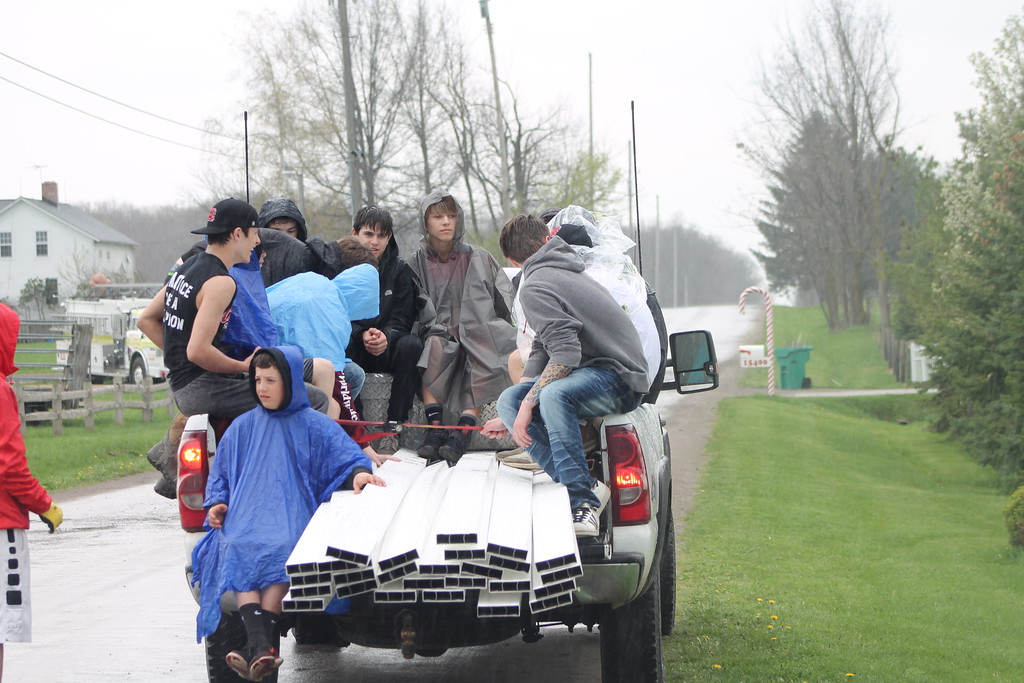 . Students from Chardon High School  take a break to grab ponchos to stay dry as the rain starts during their  community service field trip at Santa\'s Hide-A-Way Hollow in Middlefield on May 3. Kristi Garabrandt - The News-Herald