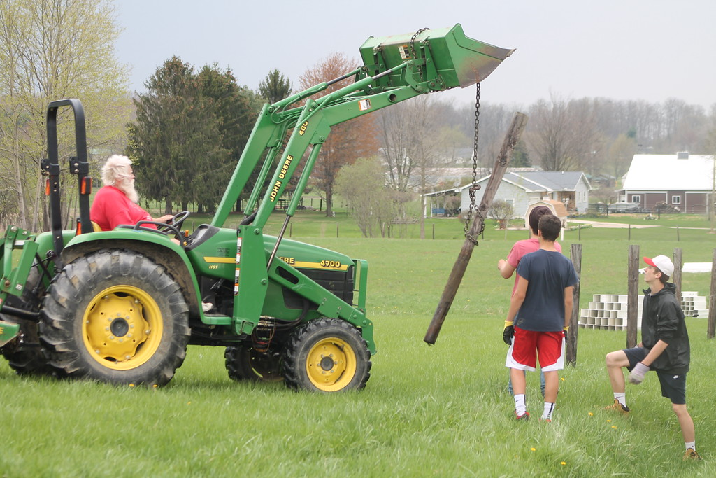 . Students from Chardon High School  help remove a wood post and wire fence to clear the way for a new vinyl one during their community service field trip at Santa\'s Hide-A-Way Hollow in Middlefield on May 3. Kristi Garabrandt - The News-Herald