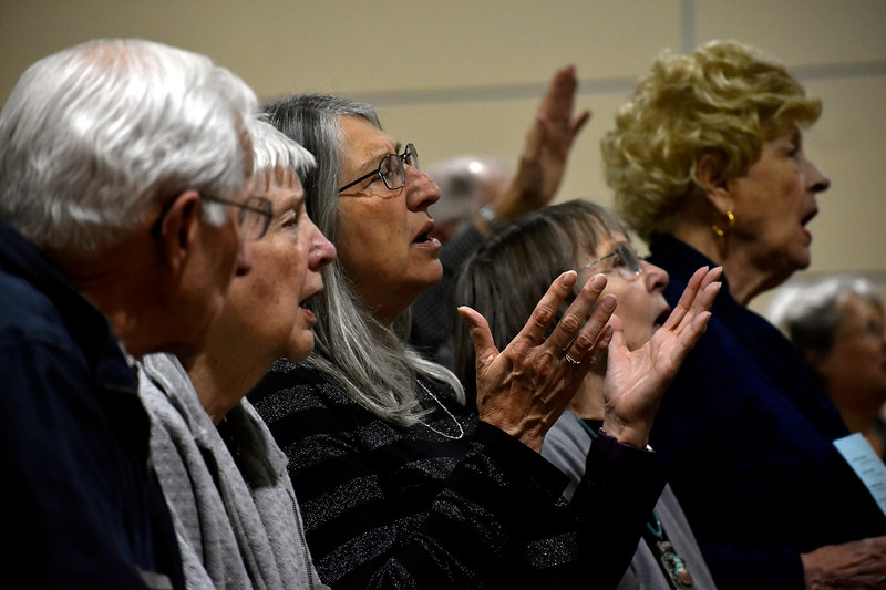 Loveland resident Teddy Irvine spreads her hands out as she sings along with the crowd during Loveland's National Day of Prayer event on Thursday, May 3, 2018, at House of Neighborly Service in Loveland. Photo by Thieng Mai/Loveland Reporter-Herald.