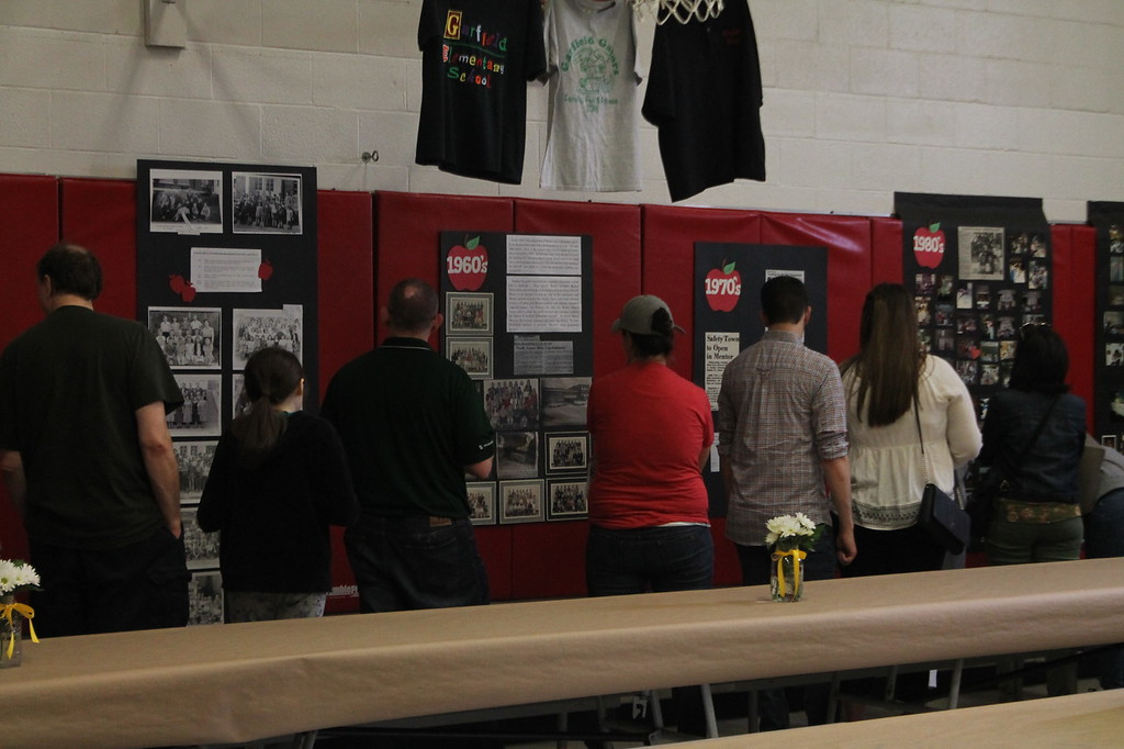 . Kristi Garabrandt � The News-Herald <br> Members of the Mentor School community  look at memory boards set up as part of the Strolling through the years display in the gymnasium at Garfield Elementary School to give the public a chance to view the schools history before it permanently closes.