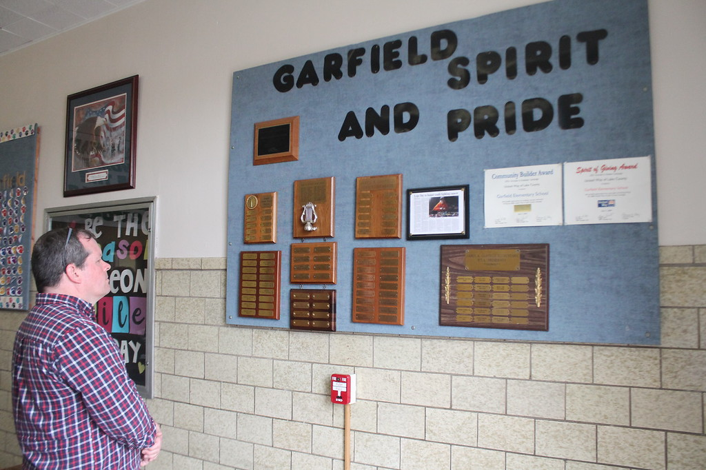 . Kristi Garabrandt � The News-Herald <br> Roger Reed looks over some of the schools recognition at  Garfield Elementary School  during the Later Gator Bash. Reed\'s son Ben is one of the students who will be attending another school in the district after Garfield permanently closes as the end of the school year.