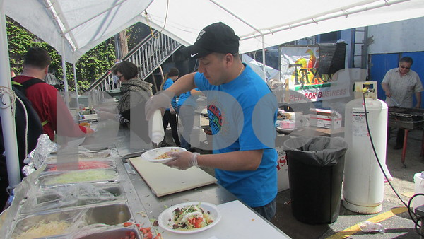 Taxco restaurant cook Miguel Diaz prepares food during the 20th Cinco de Mayo Festival on Sunday in Sycamore.